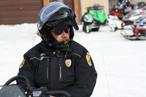 Police patrolling trails by snowmobile