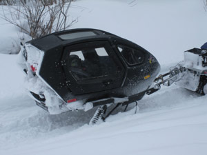 A snowmobiler towing a disabled snowmobile