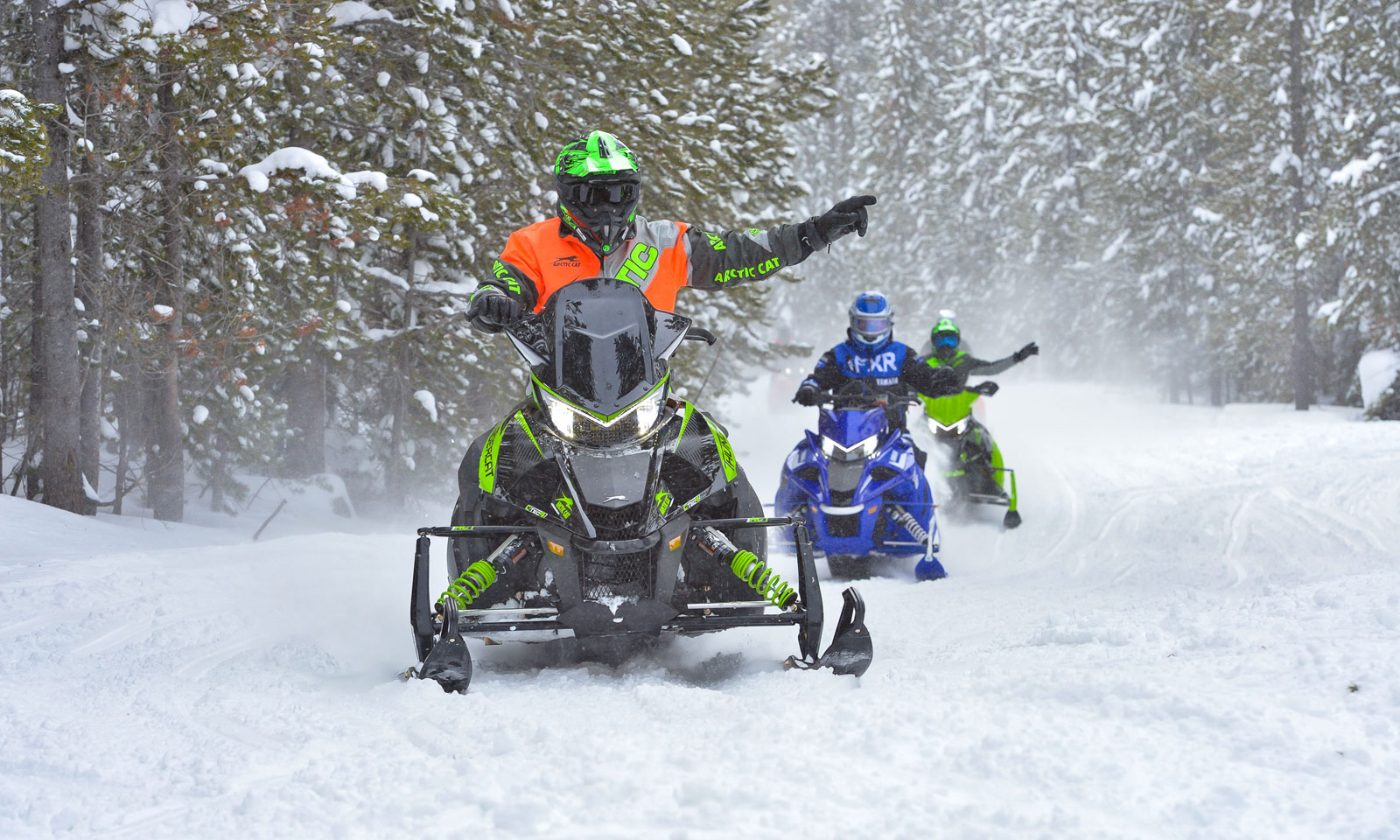 Snowmobilers showing hand signals on trail