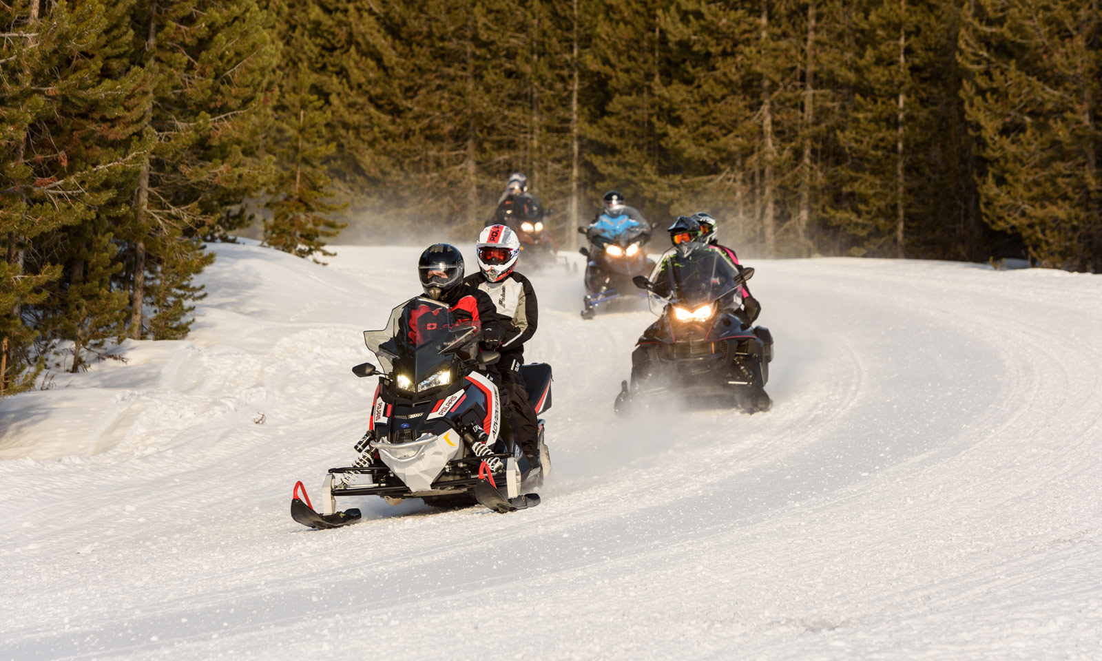 Snowmobiler riding with passenger on trail