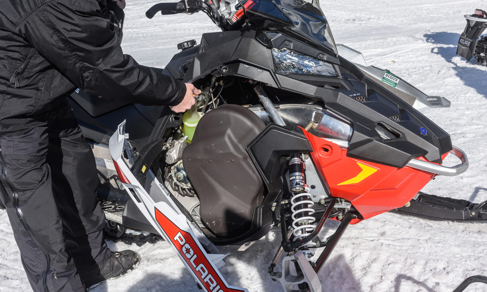 Snowmobiler checking fluid level