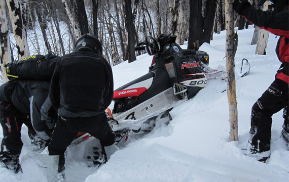 Snowmobile crashed into tree on slope