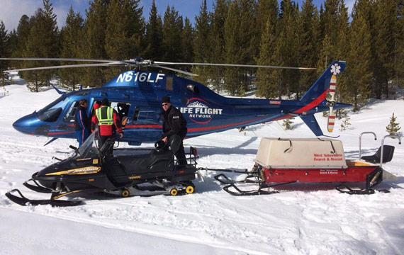Snowmobiler being transported by helicopter