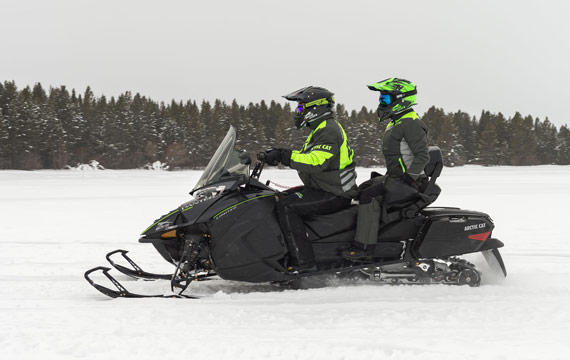 Snowmobiler riding with passenger